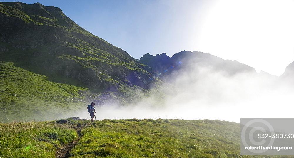 Hiker on the Schladminger Höhenweg with rising clouds of fog, Schladminger Tauern, Schladming, Steiermark, Austria, Europe