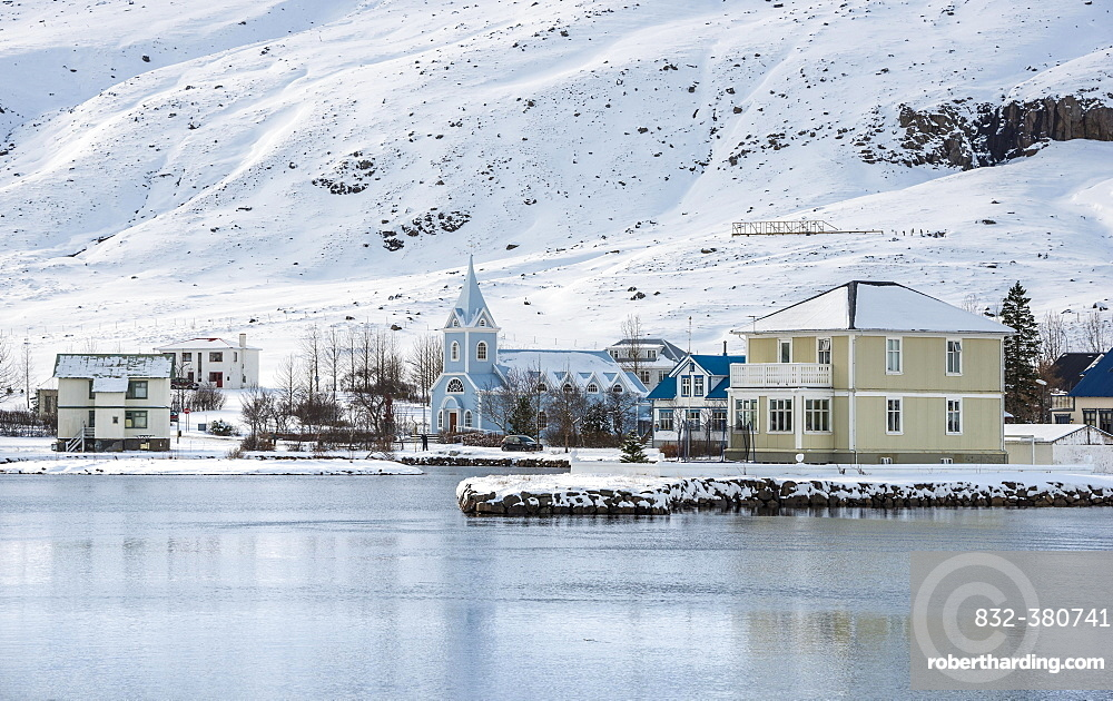 View of the blue church Seyoisfjaroarkirkja in the village Seyoisfjorour with snow, reflection in the lake Fjaroara, Austurland, East Iceland, Iceland, Europe
