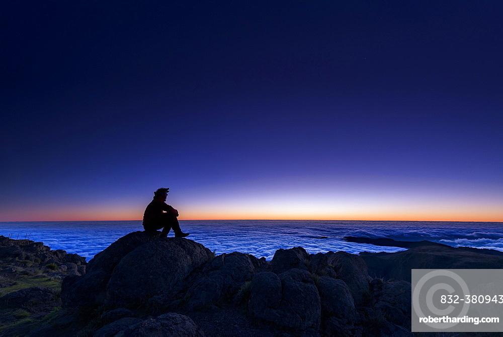 Sunrise with person on mountain peak, Pico de Arieiro, Funchal, Madeira