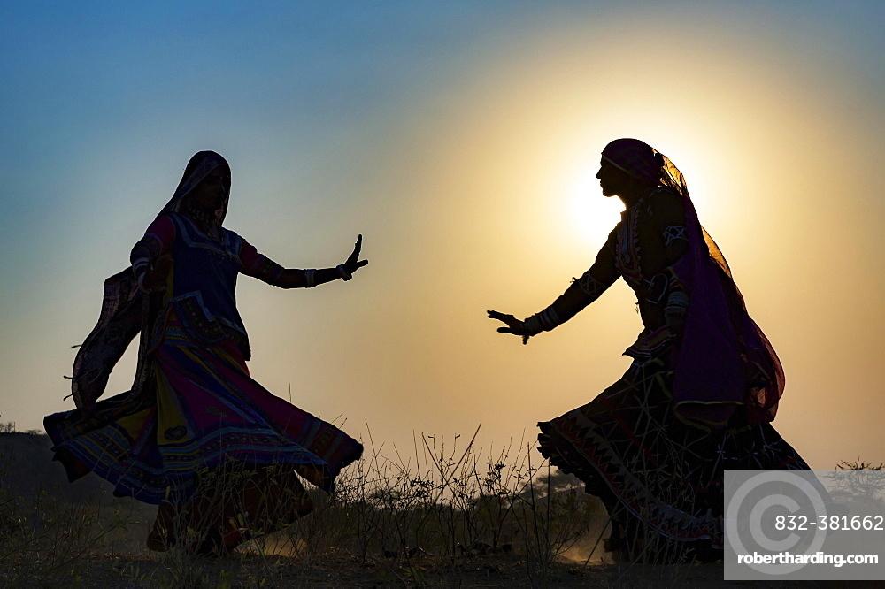 Two young women in dresses dancing in front of the setting sun, Pushkar Camel Fair, Pushkar, Rajasthan, India, Asia