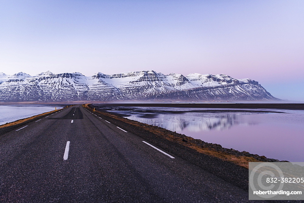 Ring road, country road by the sea, rugged volcanic landscape, mountains with snow, sunset, Iceland, Europe