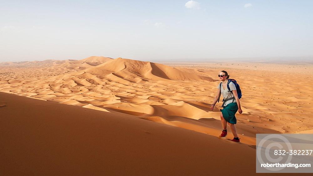 Female hiker is running on a red sand dune in the desert, dune landscape Erg Chebbi, Merzouga, Sahara, Morocco, Africa