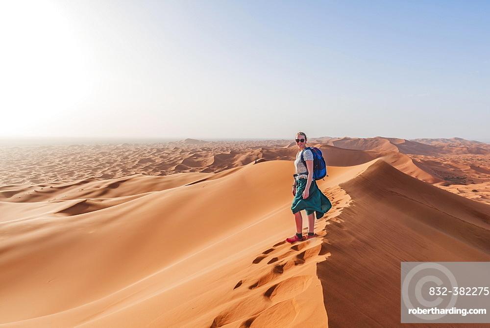 Female hiker on a red sand dune in the desert, dune landscape Erg Chebbi, Merzouga, Sahara, Morocco, Africa