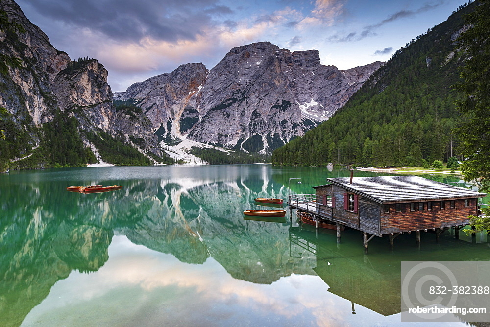 Green mountain lake with boats and boathouse, Seekogel peak in the back, water reflection, Lake Prags, Dolomites, Italy, Europe