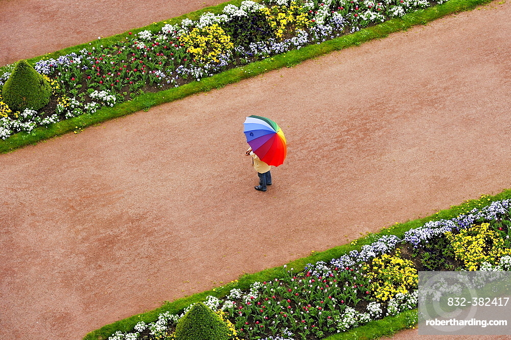 Person with umbrella in rainbow colors on a red gravel path between flower beds in the castle gardens, Fuldaer Stadtschloss City Palace, Fulda, Hesse, Germany, Europe