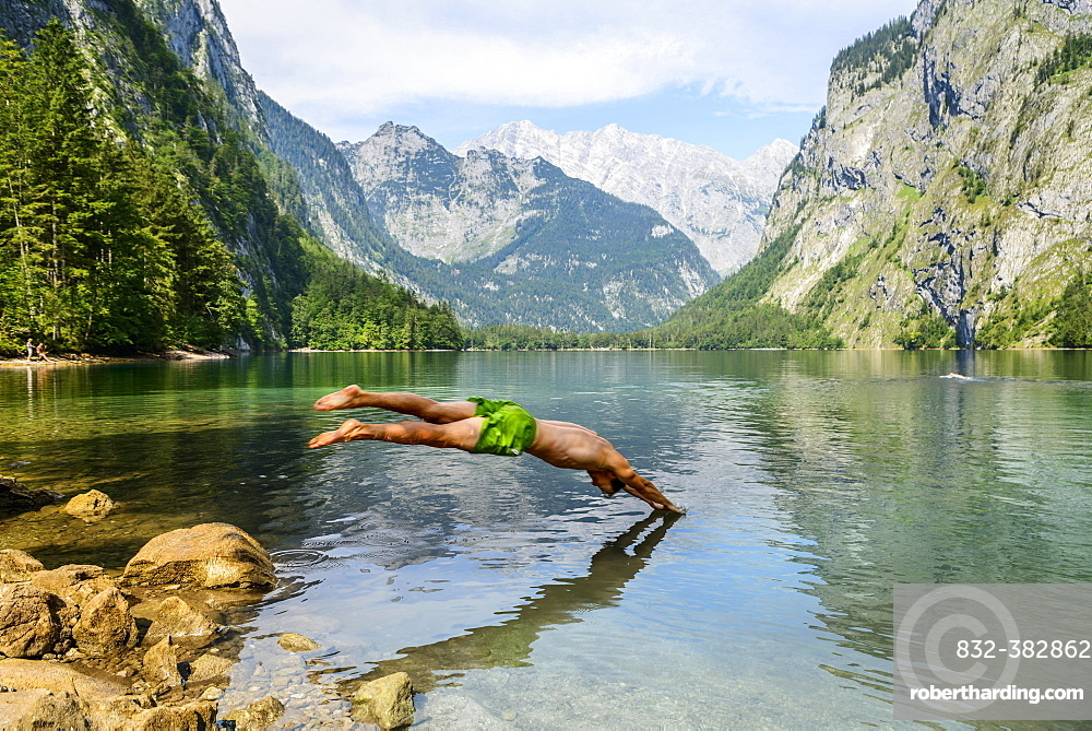 Young man jumps into Lake Obersee, swimming, mountain lake, mountain landscape, in the back Watzmann massif, Salet am Konigssee, Berchtesgaden National Park, Berchtesgadener Land, Upper Bavaria, Bavaria, Germany, Europe