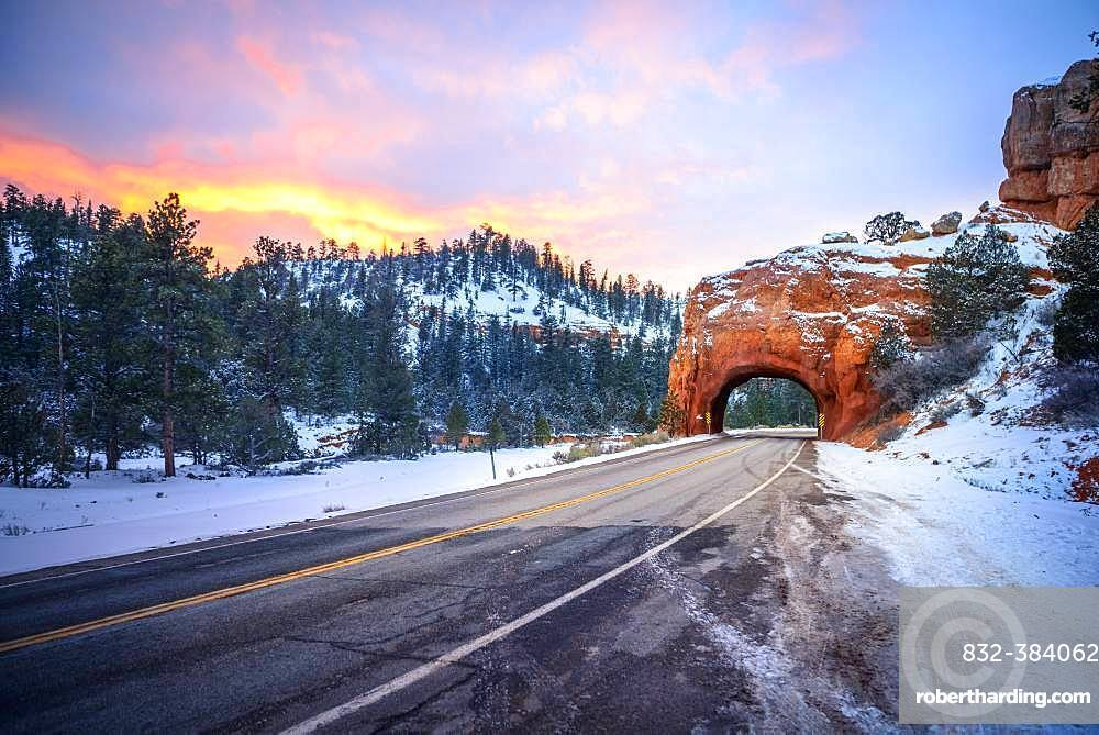 Road with tunnel through red rock arch in snow, at sunset, Highway 12, sandstone rocks, Red Canyon, Panguitch, Utah, USA, North America