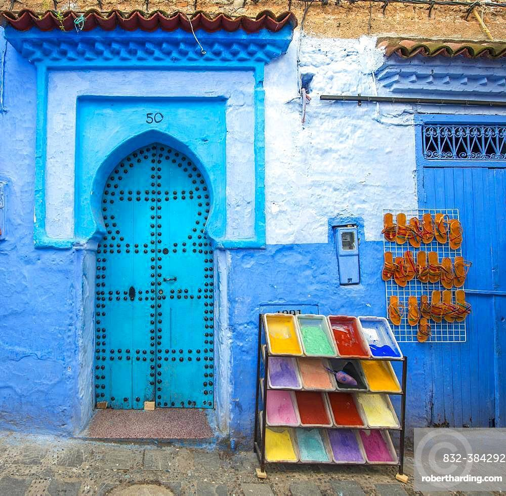 Blue entrance door with blue house facade, next to it color pigments and leather sandals for sale, Medina of Chefchaouen, Chaouen, Tanger-Tetouan, Morocco, Africa