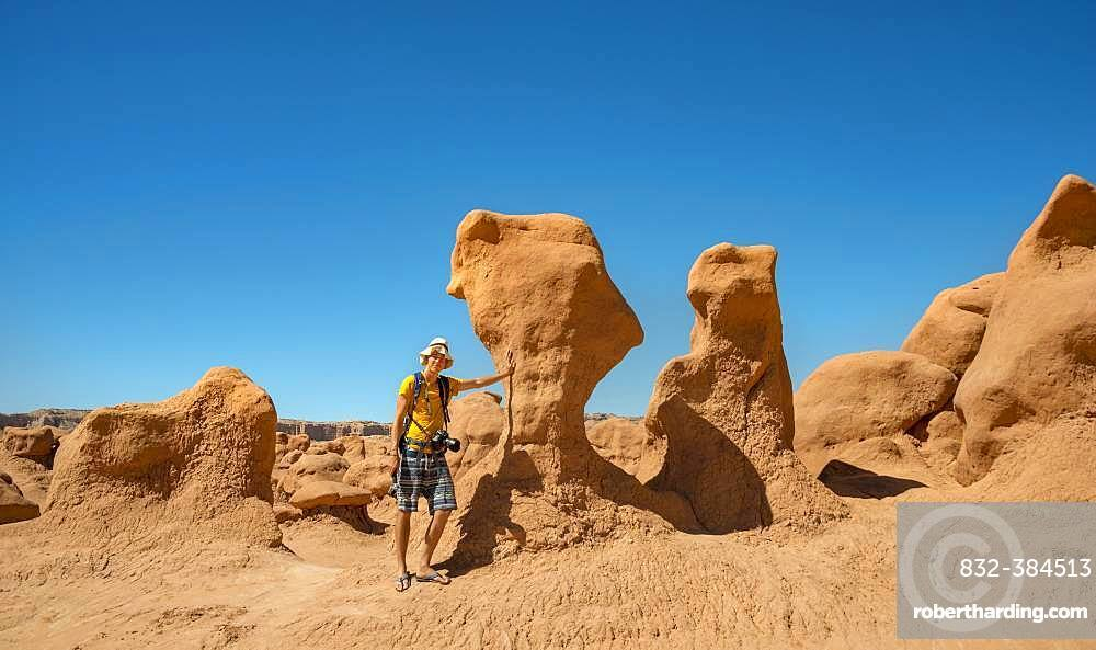 Tourist, young man next to eroded Hoodoos, rock formation of Entrada sandstone, Goblin Valley State Park, San Rafael Reef, Utah, Southwest, USA, North America