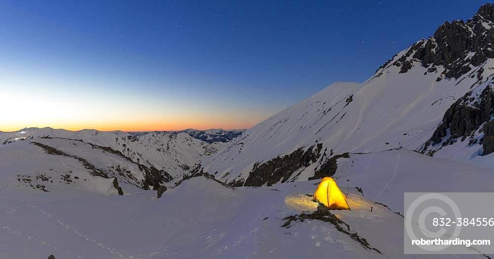 Illuminated tent in the snow on the Maedelejoch, dusk, near Kemptner hut, Allgaeuer Alps, Tyrol, Austria, Europe