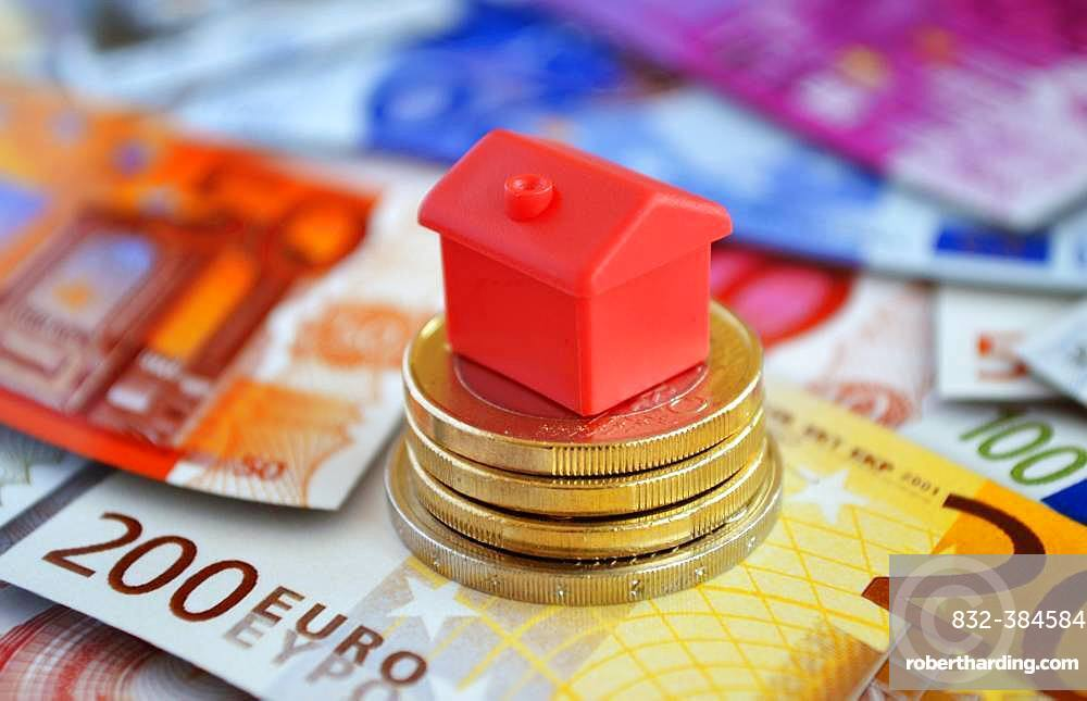 Cottage on pile with money coins and euro banknotes, symbol photo real estate financing, Germany, Europe