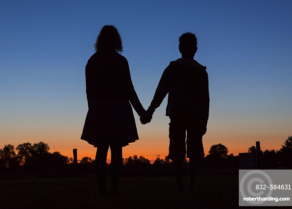 Silhouette in front of evening sky, two children holding hands, Germany, Europe