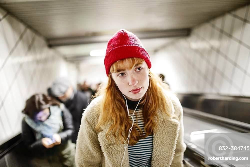 Girl, teenager, with red beanie and headphones in ear on escalator of a subway station, Cologne, North Rhine-Westphalia, Germany, Europe