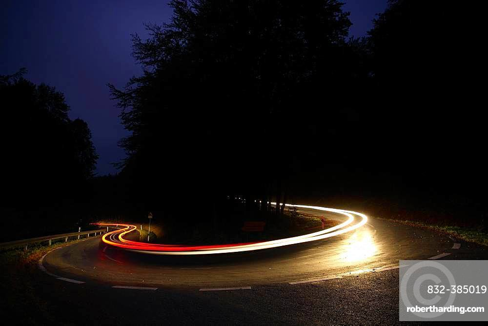 Car driving on winding country road at night, white and red light tracksHaarnadelkurve, Reinhardswald, Hesse, Germany, Europe