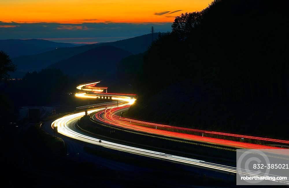 A3 motorway meanders through low mountain range landscape, light tracks at dusk, Spessart, Bavaria, Germany, Europe