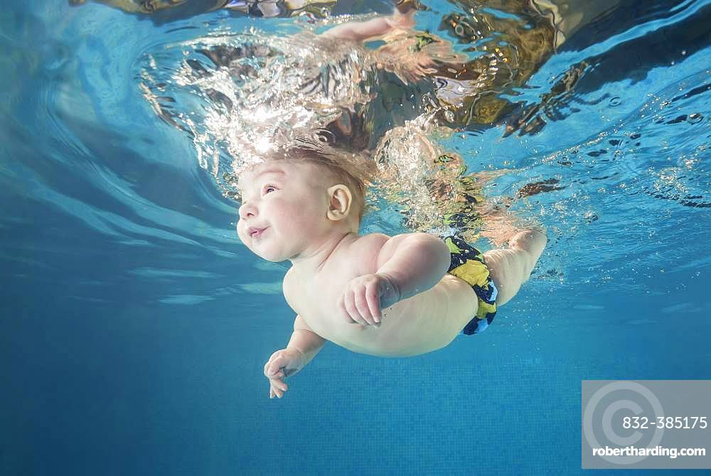 Baby boy diving in the pool, water sports for child development, Ukraine, Europe