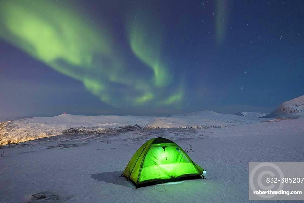 Green illuminated tent in the snow and aurora borealis above Fjellheisen, Tromsoe, Norway, Europe