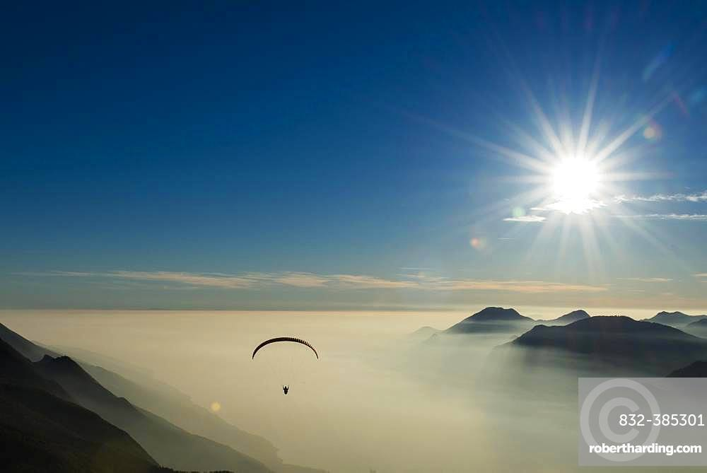 Paraglider over the mountains in clouds, near Malcesine at Lake Garda, aerial view, Veneto, Italy, Europe
