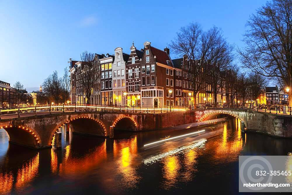 Evening mood, light tracks, boat cruises through canal with bridge, Keizersgracht and Leidsegracht, canal with historic houses, Amsterdam, North Holland, Netherlands