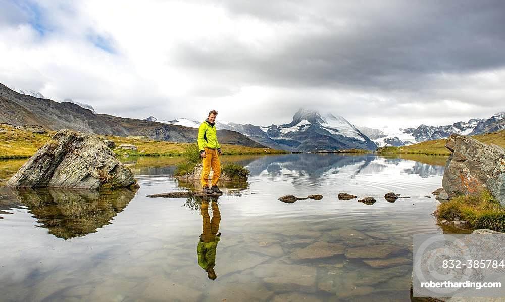Hiker walks over stones in the water, Lake Stellisee, cloudy Matterhorn, Valais, Switzerland, Europe