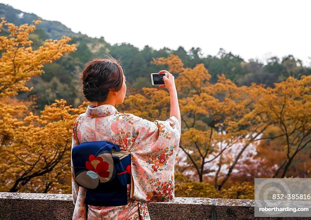 Japanese woman dressed with kimono, photographed with a mobile phone, at Kiyomizu-dera Temple, Higashiyama, Kyoto, Japan, Asia