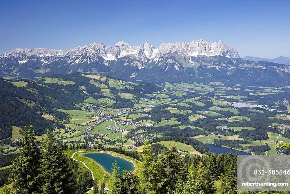 View from the Hahnenkamm summit onto impounding reservoir and Lake Schwarzsee, near Kitzbuehel, behind Wilder Kaiser, Kaiser Mountains, Alps, Tyrol, Austria, Europe