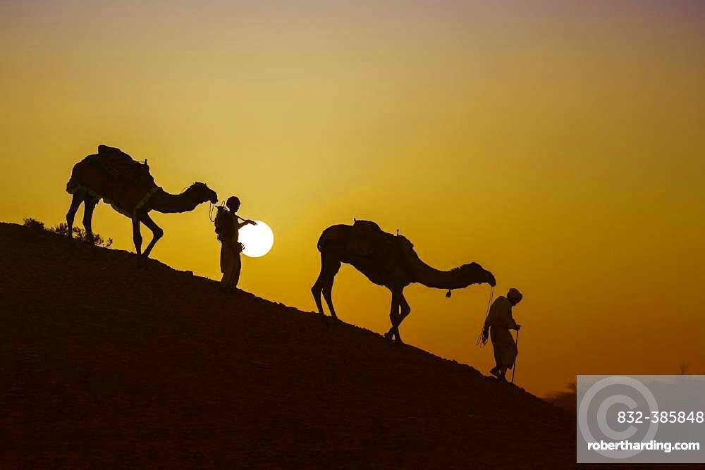 Two Rabari men going down a dune at sunset, silhouettes, Great Rann of Kutch, Gujarat, India, Asia