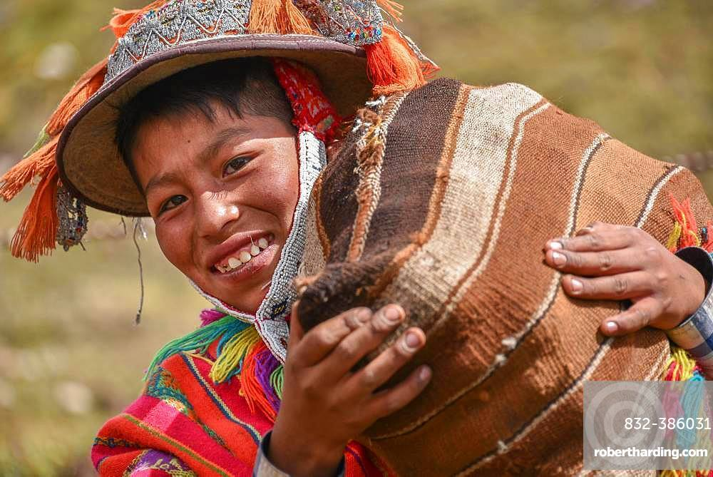 Indio boy with hat with colorful ribbons and poncho wearing sack with potatoes, portrait, at Cusco, Peru, South America