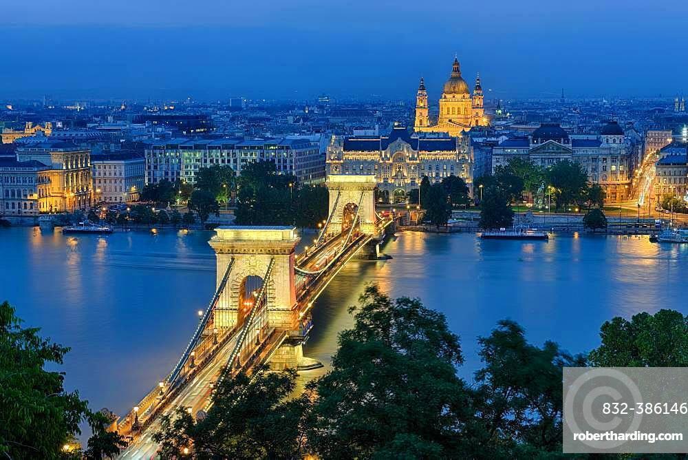 Chain bridge with Gresham Palace and St. Stephen's Basilica, illuminated, dusk, Budapest, Hungary, Europe
