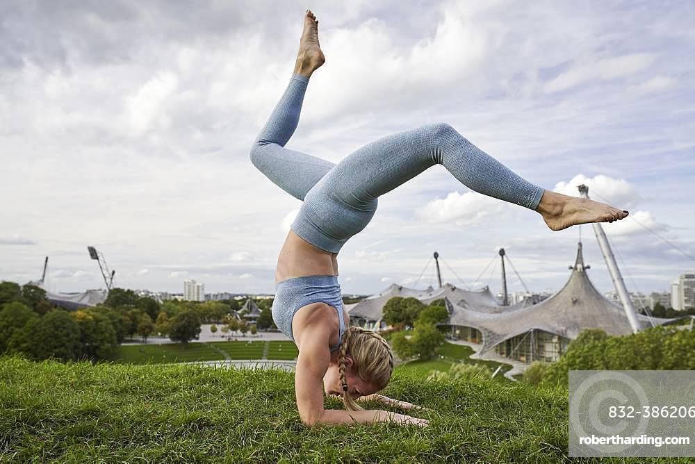 Young woman doing yoga, gymnastics, Olympiapark, Munich, Germany, Europe