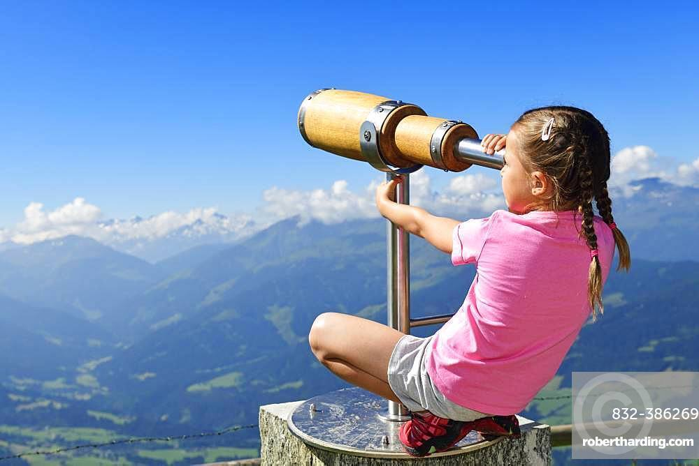 Girl looking through a wooden telescope, summit panorama path of the Hohe Salve, Hopfgarten, Brixental, Kitzbuehel Alps, Tyrol, Austria, Europe