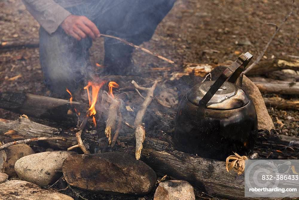 Coffee kettle on the campfire, behind it the legs of a person kneeling at the campfire, Haerjedalen, Sweden, Europe