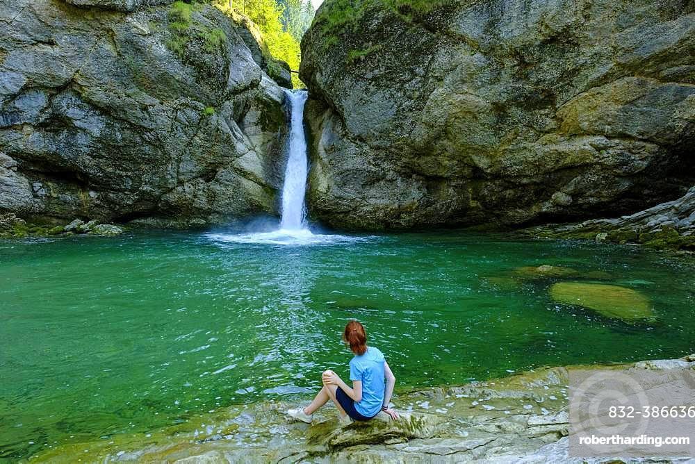 Young woman sitting in front of Buchenegger waterfalls near Oberstaufen, Oberallgaeu, Allgaeu, Swabia, Bavaria, Germany, Europe