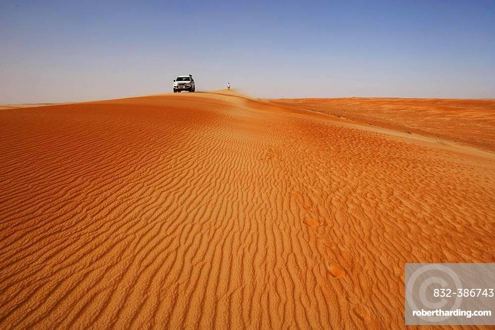 Off-road vehicle and tourist on a sand dunes, desert safari, desert Rimal Wahiba Sands, Oman, Asia