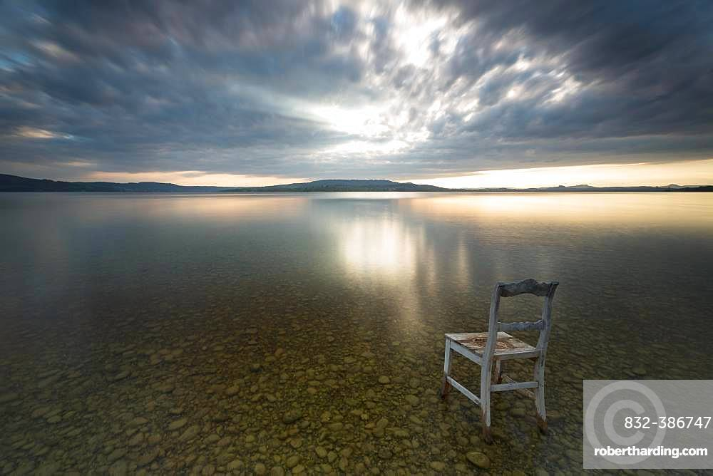Old wooden chair in water with cloudy sky, Lake Constance, Baden-Wuerttemberg, Germany, Europe
