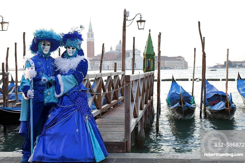 Blue couple standing in front of gondolas, carnival in Venice, church San Giorgio Maggiore in the back, Venice, Italy, Europe
