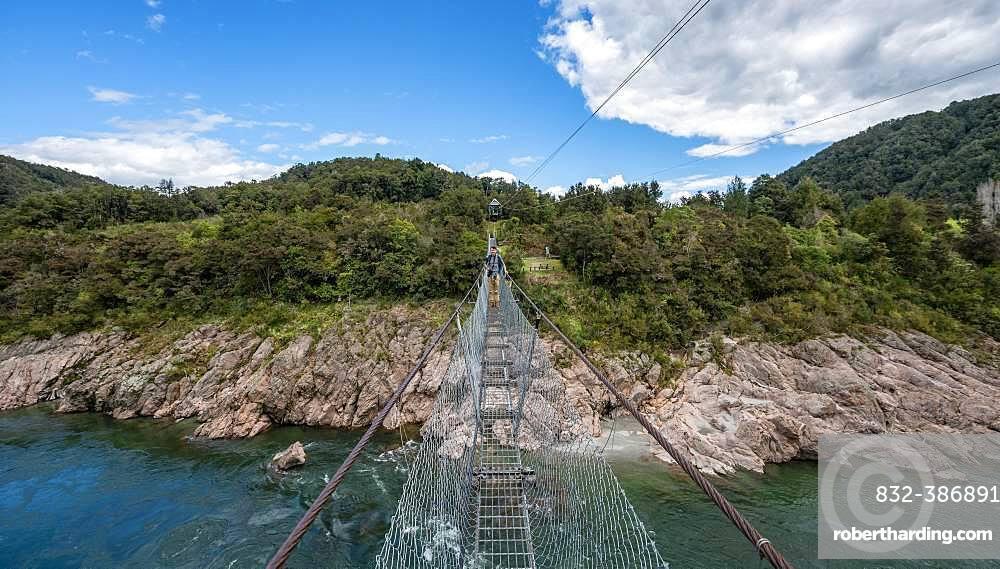 Young man on suspension bridge over Buller River, Buller Gorge Swing Bridge, Inangahua, West Coast, South Island, New Zealand, Oceania