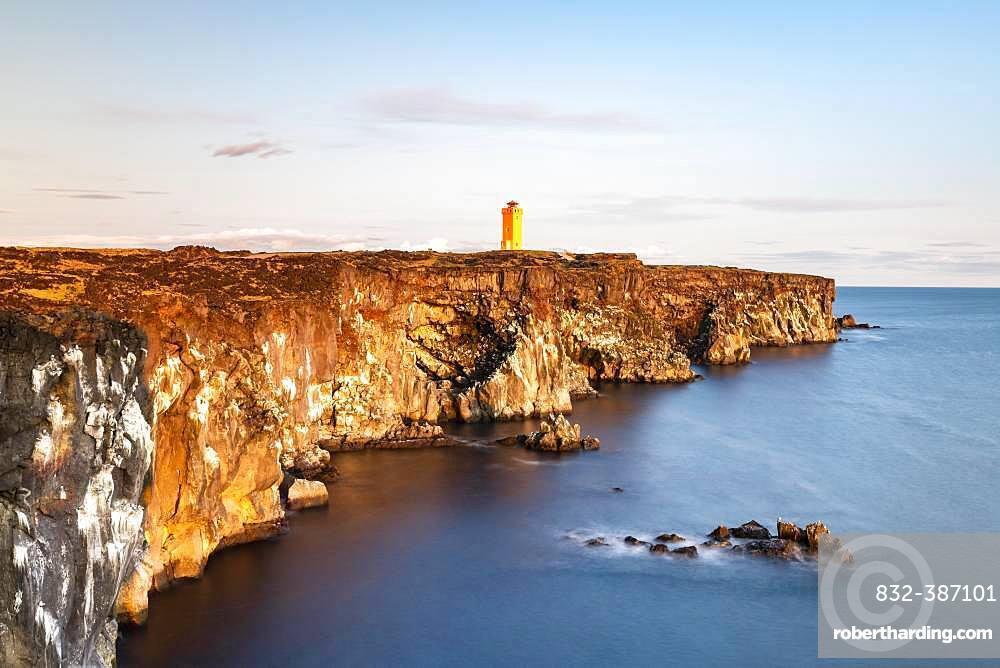 Orange lighthouse of Oendverdarnes stands at cliff coast, rocky coast of lava rock, long time exposure, Oendveroarnes, Snaefellsjoekull National Park, Snaefellsnes Peninsula, Snaefellsnes, Vesturland, Iceland, Europe