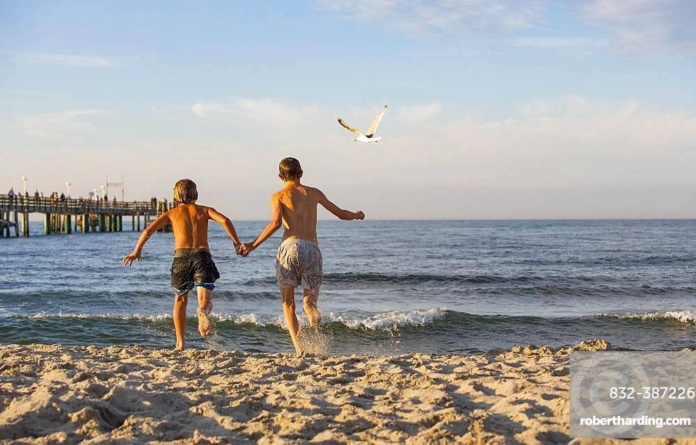 Two young people run into the water at the Baltic Sea beach, Kuehlungsborn, Mecklenburg-Western Pomerania, Germany, Europe