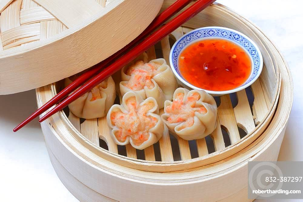 Dim Sum, filled dumplings with chopsticks and chilli sauce in steam baskets, Germany, Europe