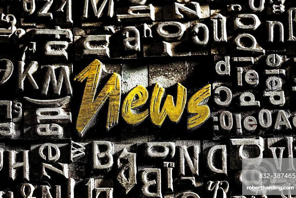 Old lead letters with golden writing show the word News, Germany, Europe