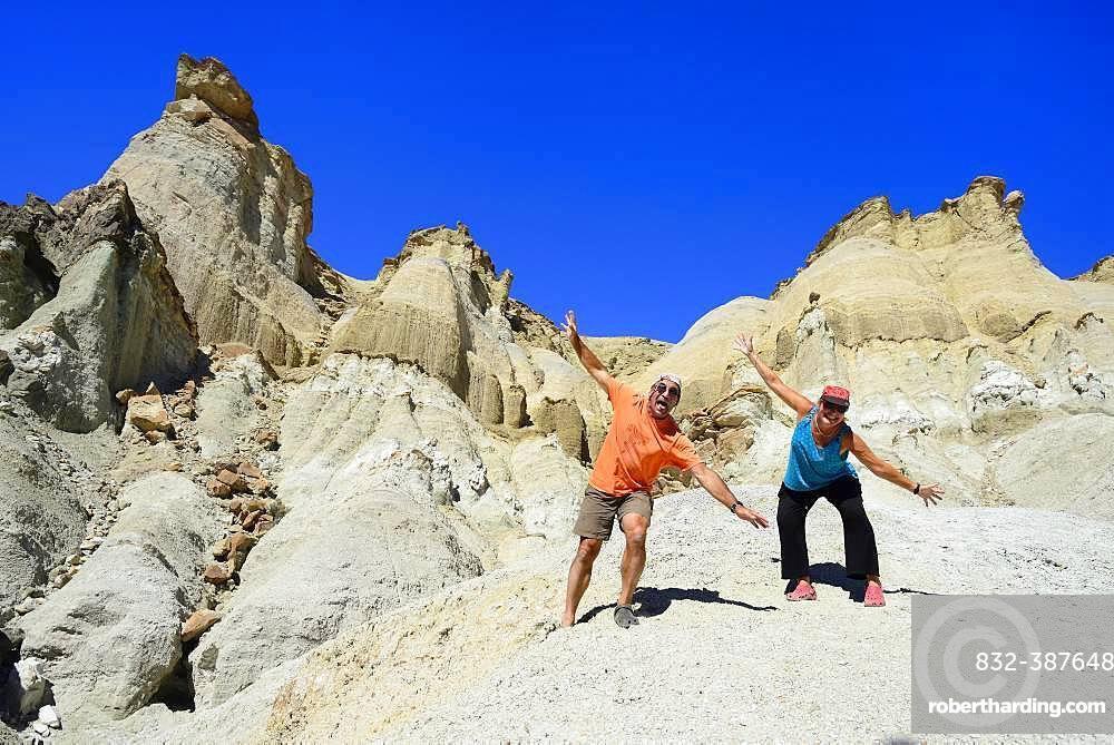 Two tourists at the bizarre rock formations of Cerro Alcazar, Calingasta, San Juan Province, Argentina, South America