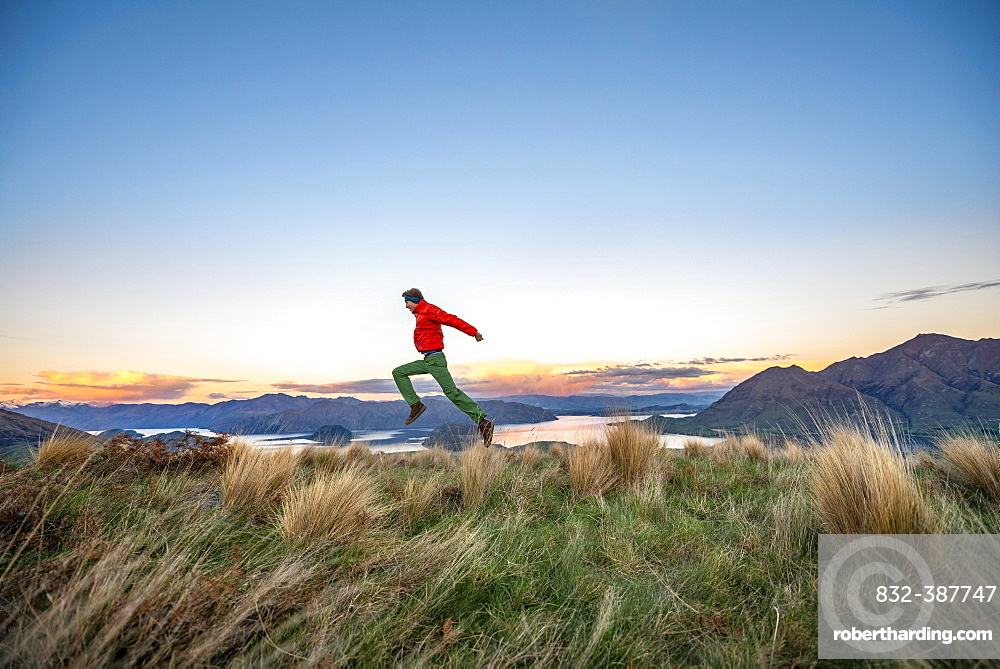Hiker jumps into the air, panoramic view of Wanaka Lake and mountains at sunset, Rocky Peak, Glendhu Bay, Otago, South Island
