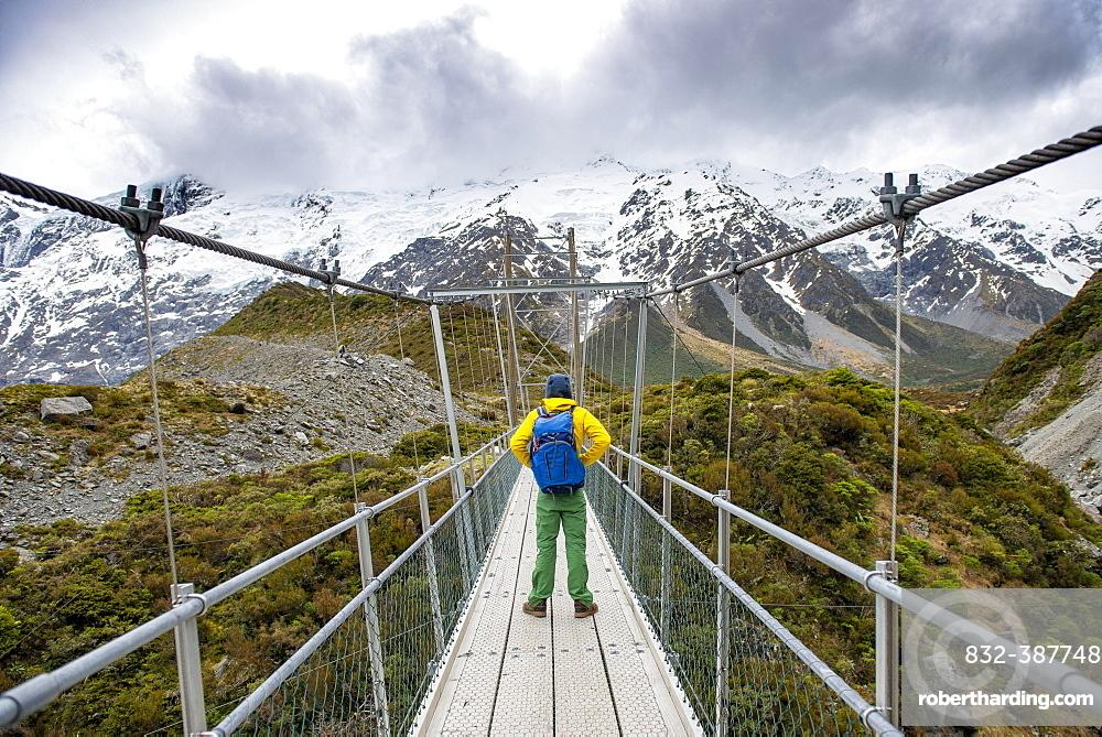 Hiker crosses suspension bridge over Hooker River, Hooker Valley, Mount Cook National Park, Canterbury, New Zealand, Oceania