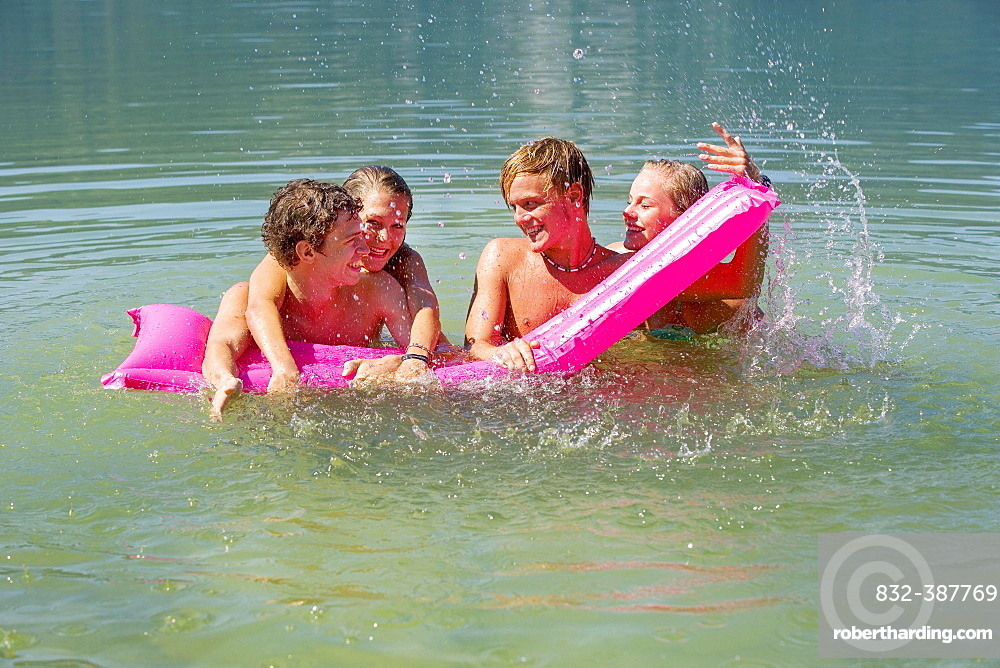 Four teenagers on an air mattress in water have fun bathing, 18 years, Mondsee, Upper Austria, Austria, Europe