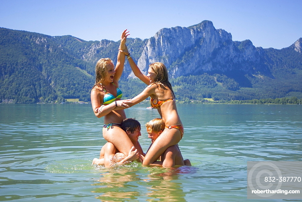 Four teenagers in the water have fun swimming, 18 years, Mondsee, Upper Austria, Austria, Europe