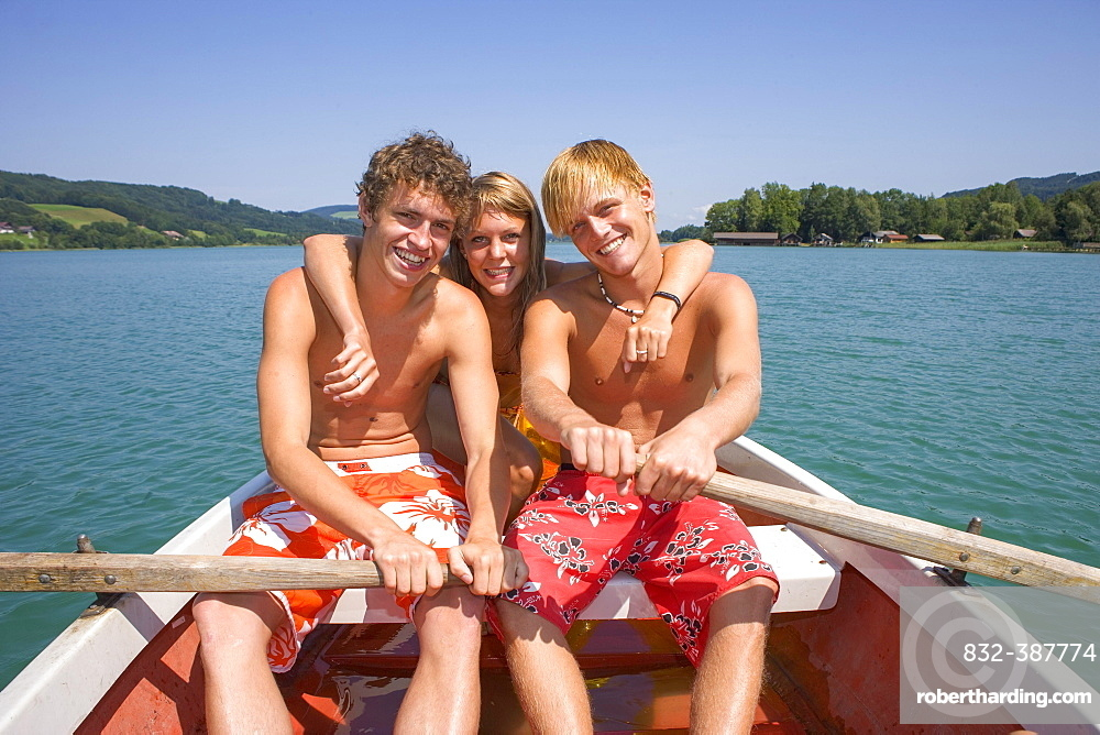 Three teenagers sitting in a rowing boat, 18 years, Irrsee, Upper Austria, Austria, Europe