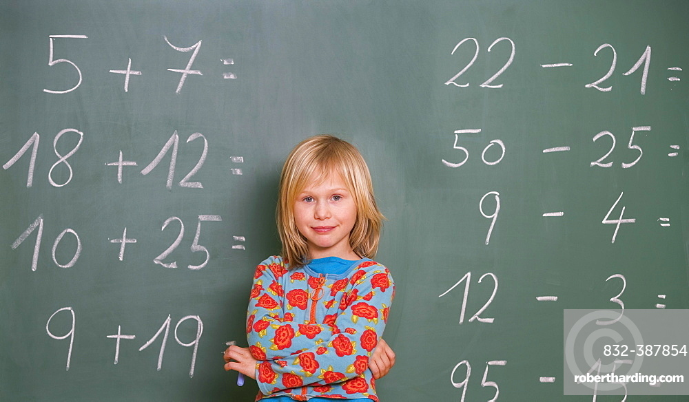 Schoolgirl stands in front of the blackboard in the classroom and calculates, Austria, Europe