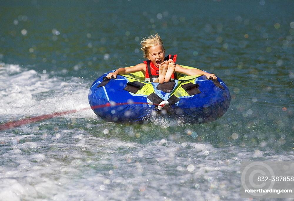 Girl rafting with water hoops in a lake, Lake Mondsee, Upper Austria, Austria, Europe