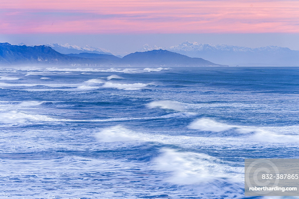 Leaking waves of the ocean under a pink evening sky with mountain silhouette, Punakaiki, Paparoa National Park, West Coast Region, New Zealand, Oceania